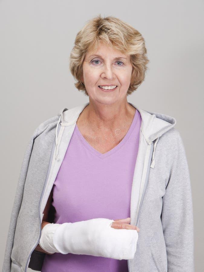 Mulher sênior com o braço direito no molde do branco foto de stock