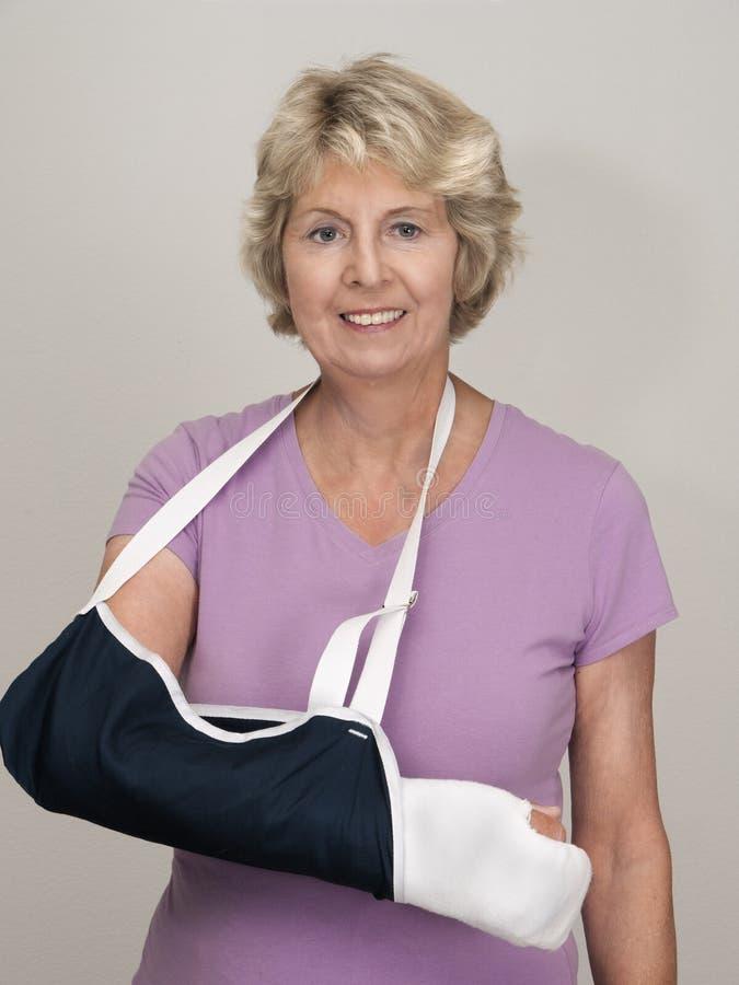 Mulher sênior com o braço no molde e no estilingue imagens de stock