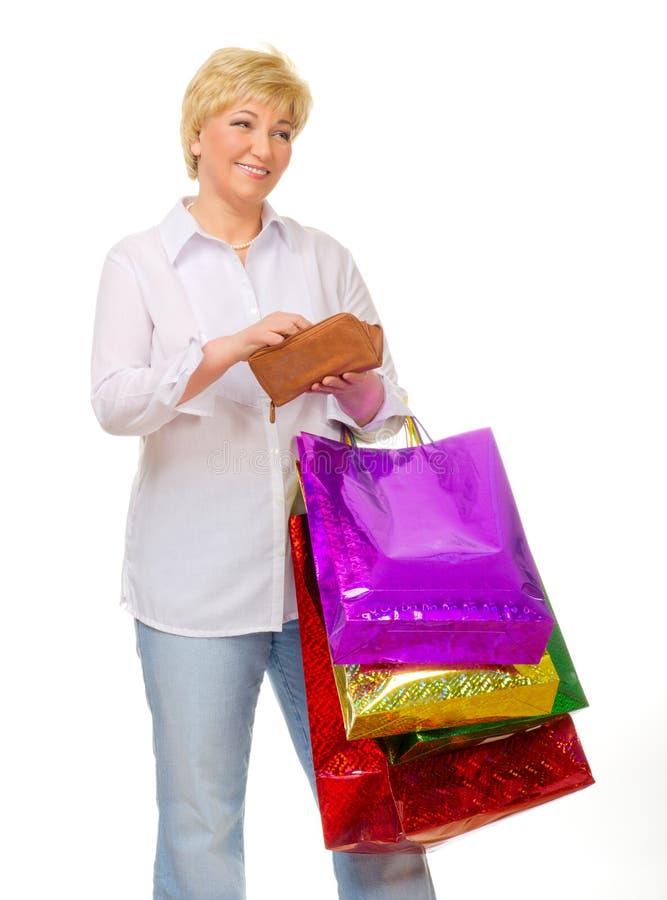 Mulher sênior com sacos e carteira foto de stock royalty free