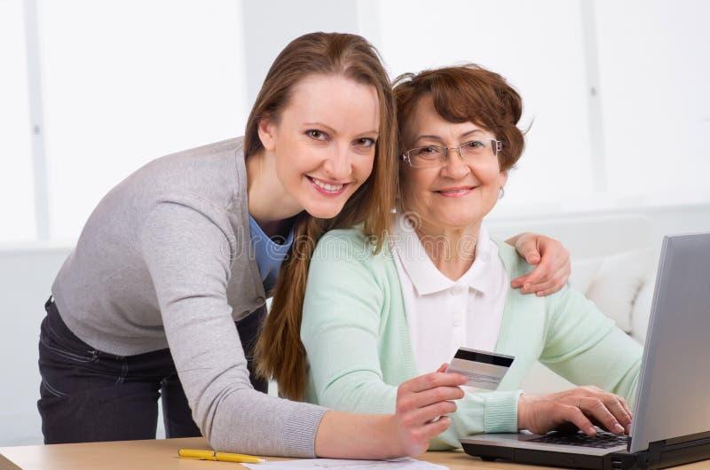 Mulher sênior com seu comprar em linha da filha imagem de stock
