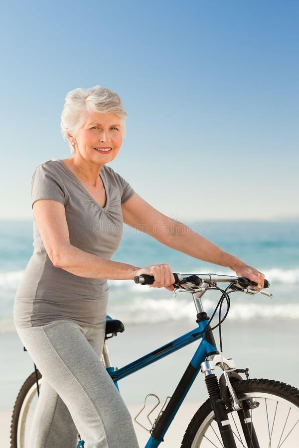 Mulher sênior com sua bicicleta imagem de stock royalty free