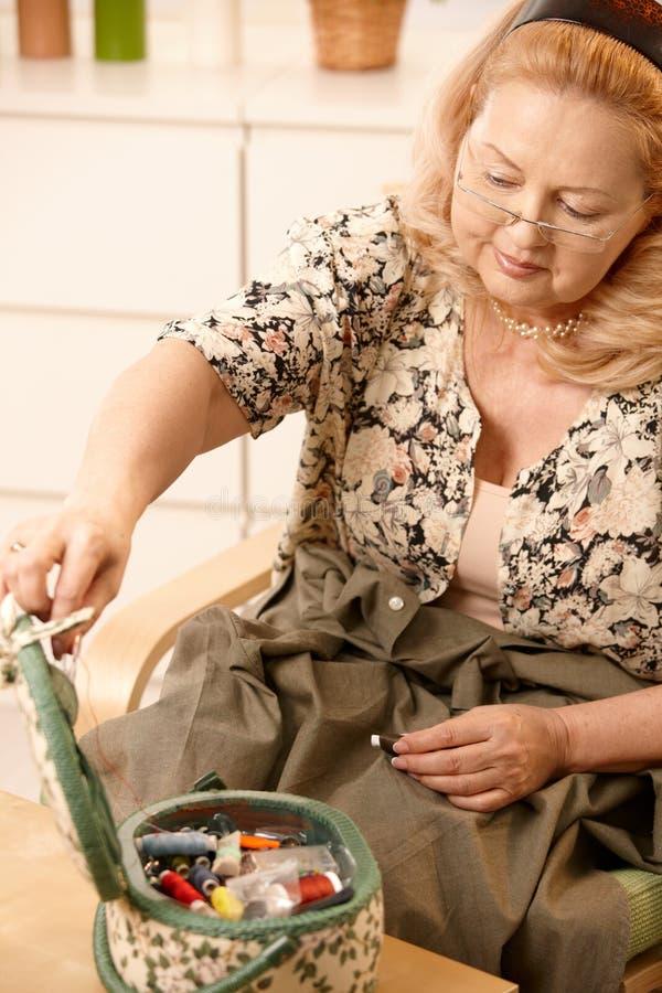 Mulher sênior de sorriso com jogo sewing imagens de stock