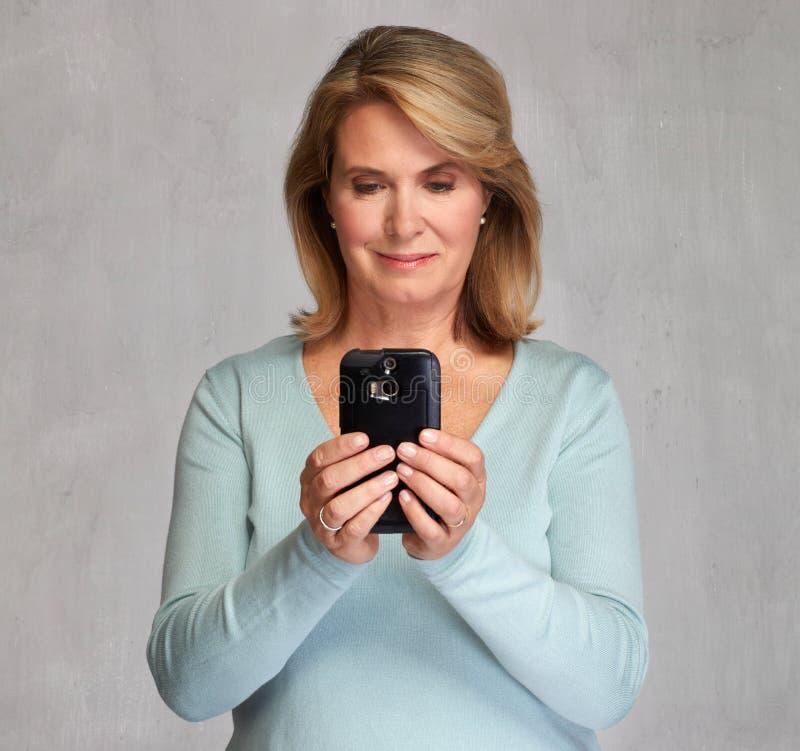 Mulher sênior de sorriso com Smartphone fotos de stock royalty free