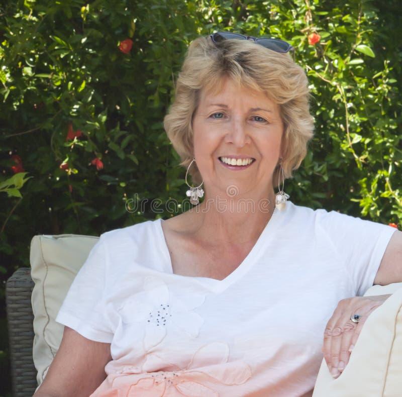 Mulher sênior de sorriso que senta-se no jardim fotos de stock