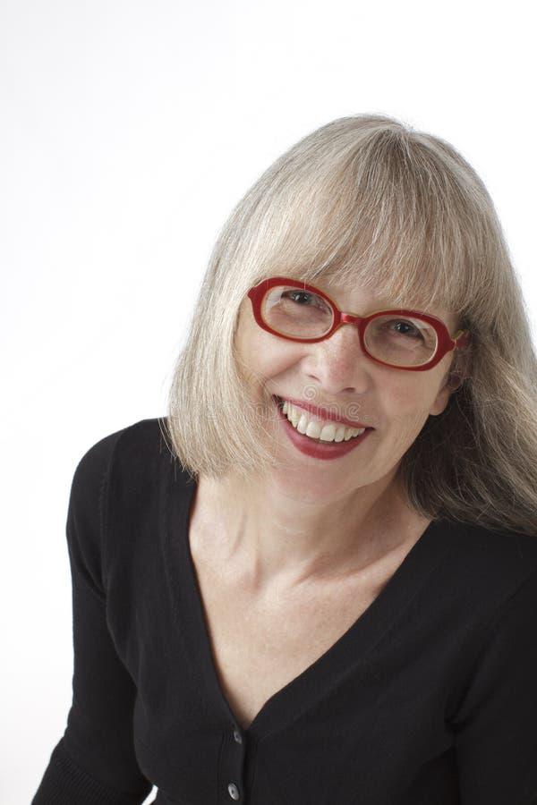 Mulher sênior de sorriso vibrante com vidros vermelhos. fotos de stock