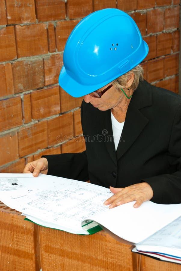 Mulher sênior do arquiteto com projeto foto de stock