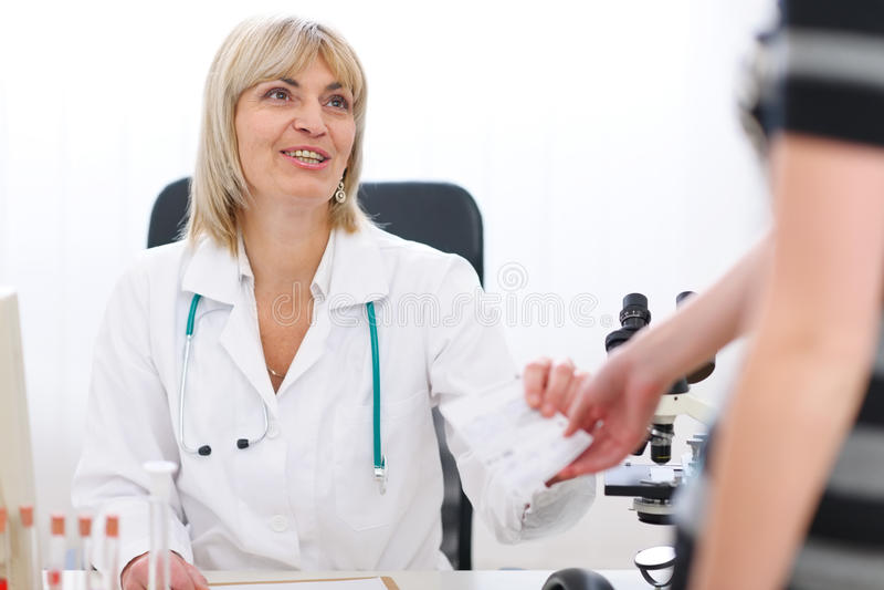 Mulher sênior do doutor que dá a prescrição ao paciente fotografia de stock royalty free