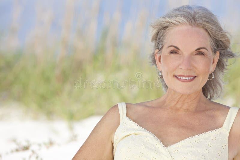 Mulher sênior elegante atrativa que senta-se em uma praia foto de stock