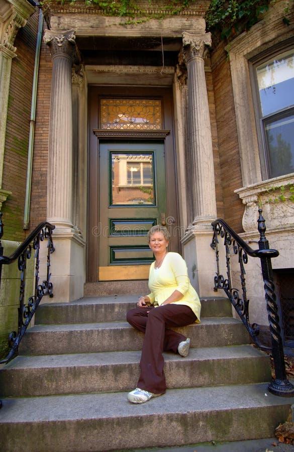 Mulher sênior em etapas do apartamento da cidade foto de stock
