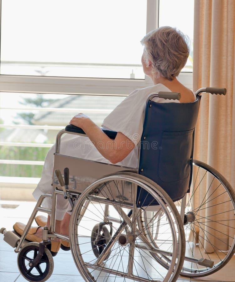 Mulher sênior em sua cadeira de rodas fotografia de stock royalty free