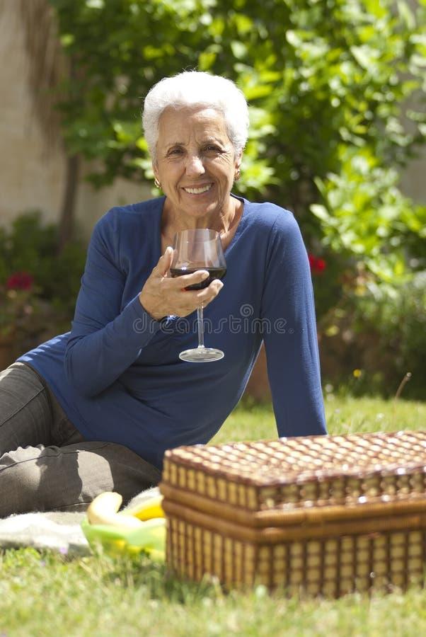 Mulher sênior encantadora que aprecia um vidro do vinho vermelho fotografia de stock royalty free