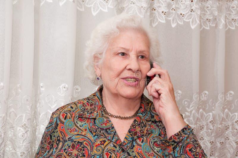A mulher sênior fala no telefone móvel imagem de stock royalty free
