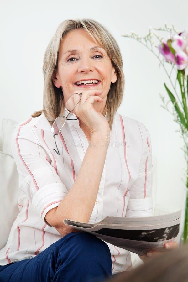 Mulher sênior feliz com jornal fotos de stock royalty free