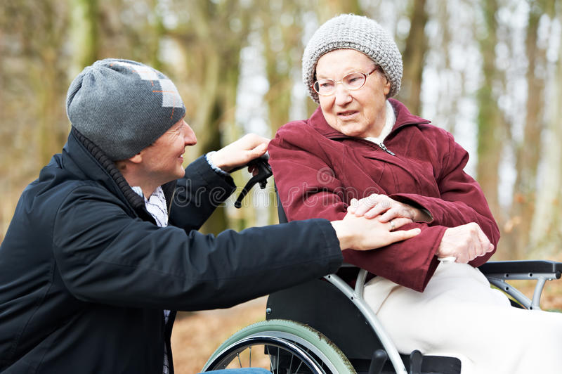 Mulher sênior idosa na cadeira de rodas com filho cuidadoso imagem de stock