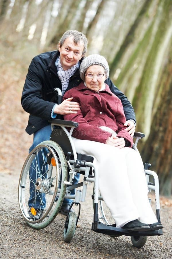 Mulher sênior idosa na cadeira de rodas com filho cuidadoso fotografia de stock royalty free