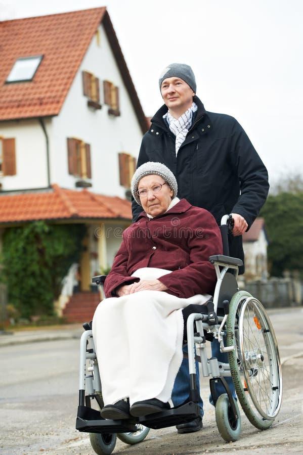 Mulher sênior idosa na cadeira de rodas com filho cuidadoso foto de stock royalty free