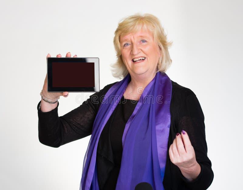A mulher sênior indica o computador da tabuleta fotografia de stock royalty free