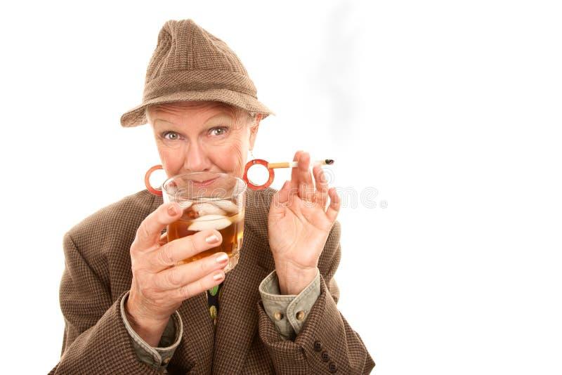Mulher sênior no arrasto com cigarro e álcool imagem de stock royalty free