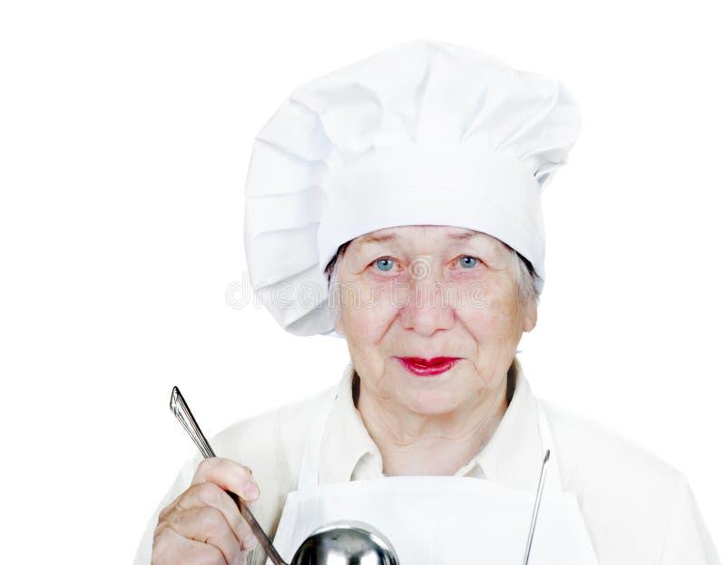 Mulher sênior no chapéu do cozinheiro chefe imagem de stock