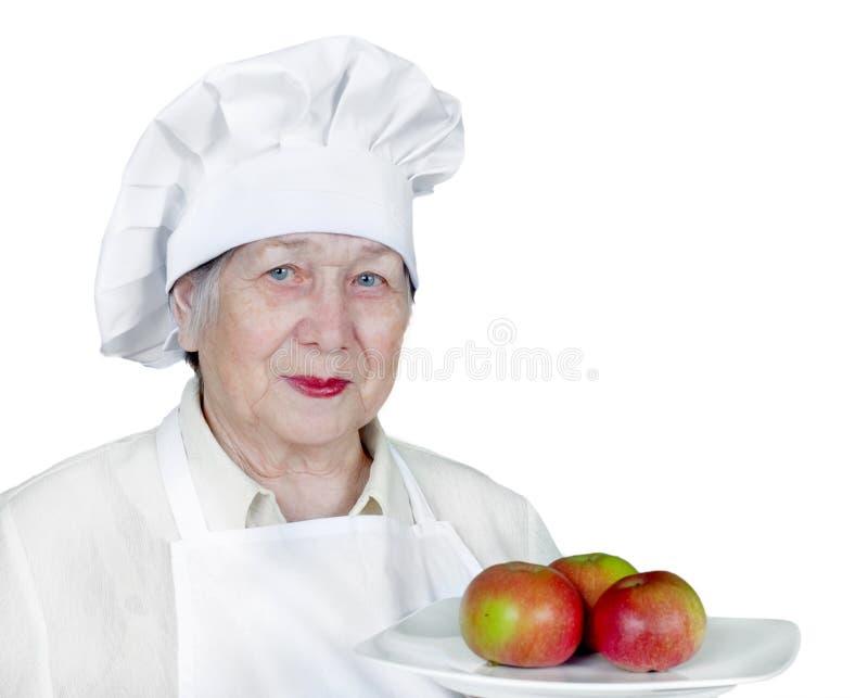 Mulher sênior no chapéu do cozinheiro chefe imagem de stock royalty free