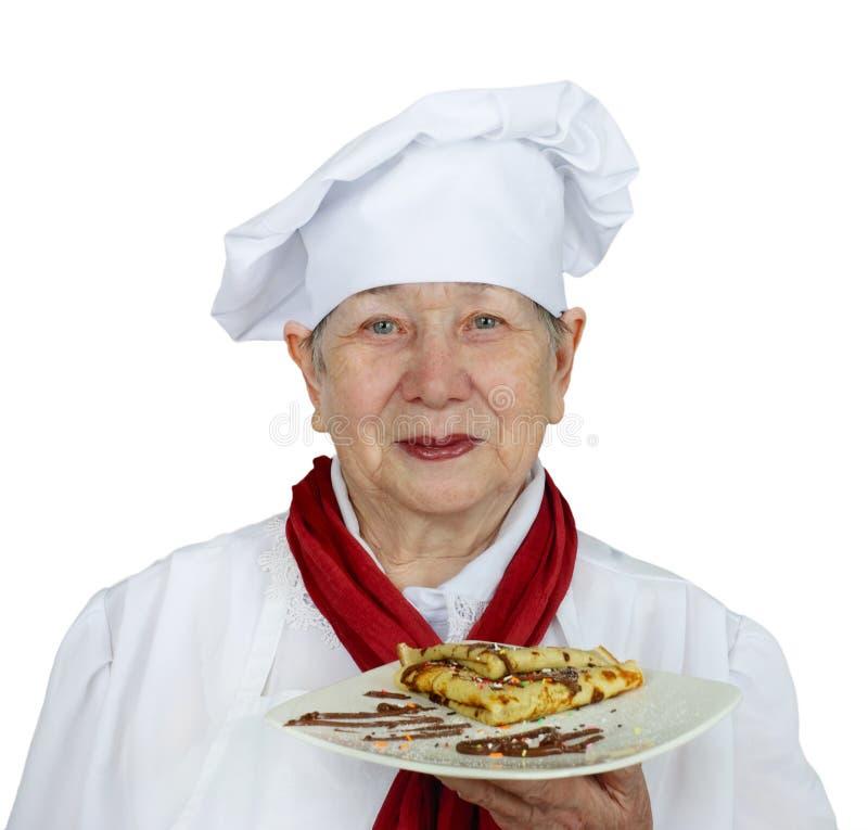 Mulher sênior no chapéu do cozinheiro chefe fotos de stock