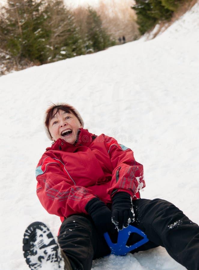 Mulher sênior no sledge - atividade da neve do inverno fotos de stock