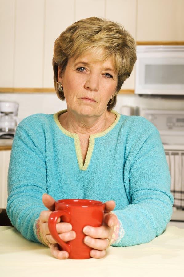 A mulher sênior, olhando infeliz, prende uma caneca de café imagens de stock royalty free