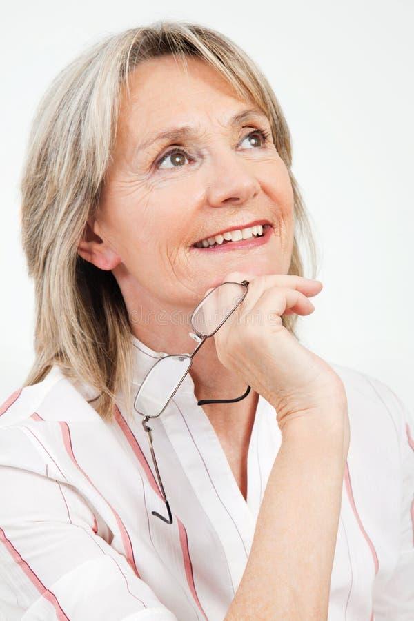 Mulher sênior pensativa de sorriso fotografia de stock royalty free