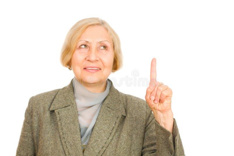 Mulher sênior que aponta para cima fotos de stock