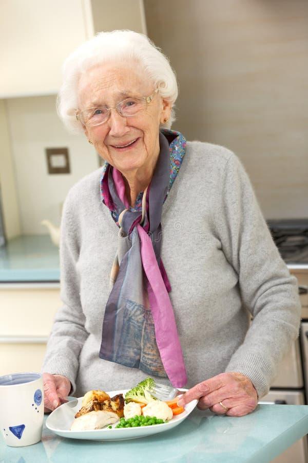 Mulher sênior que aprecia a refeição na cozinha imagem de stock royalty free
