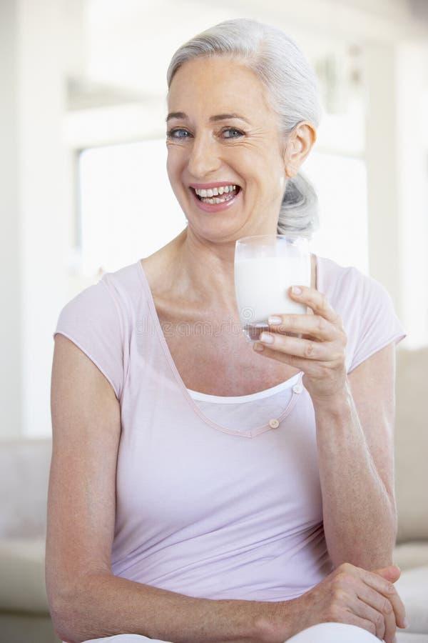 Mulher sênior que bebe um vidro do leite imagens de stock royalty free