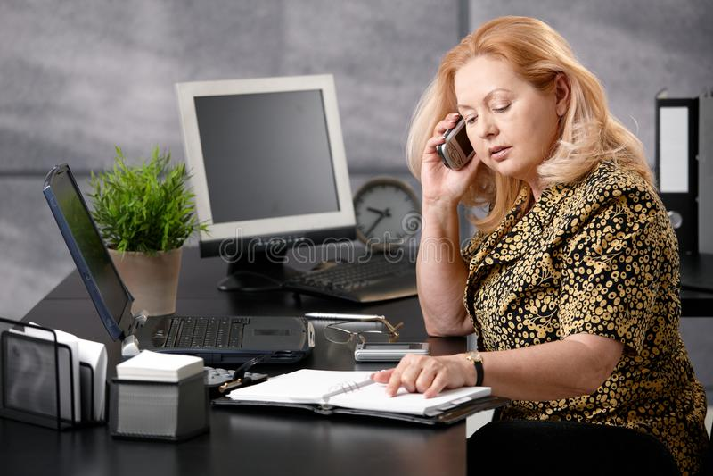 Mulher sênior que chama no escritório foto de stock royalty free