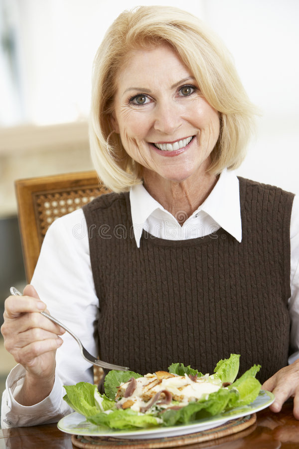 Mulher sênior que come a salada imagem de stock royalty free