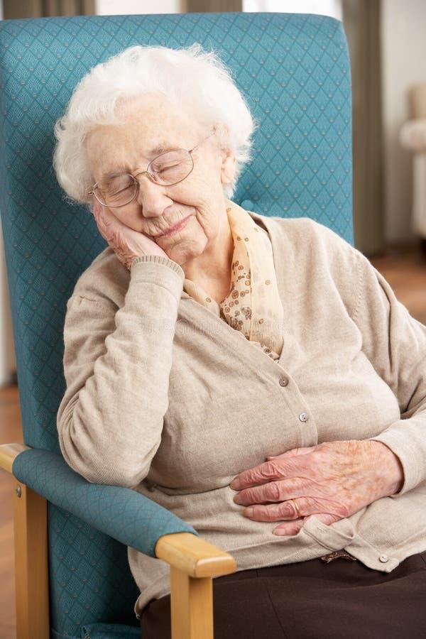 Mulher sênior que descansa na cadeira fotografia de stock royalty free