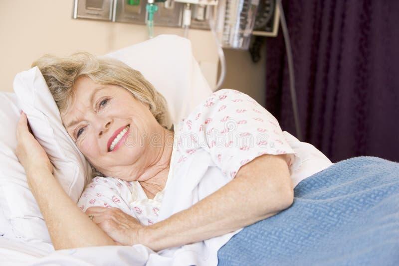 Mulher sênior que encontra-se na cama de hospital foto de stock royalty free