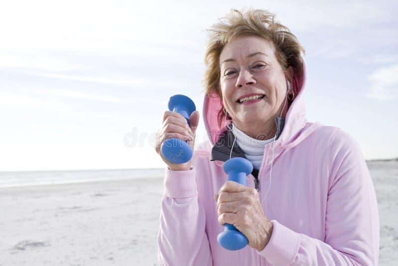 Mulher sênior que exercita com pesos da mão na praia fotos de stock royalty free