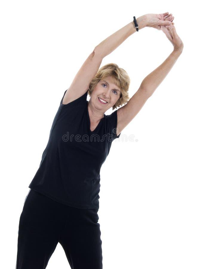 Mulher sênior que faz o exercício do estiramento foto de stock