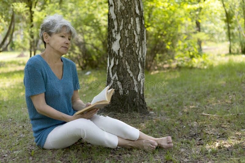 Mulher sênior que lê um livro fotografia de stock royalty free