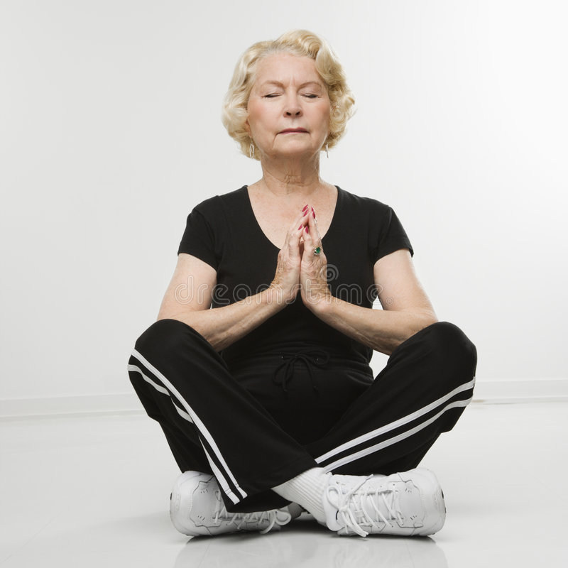 Mulher sênior que meditating. fotos de stock