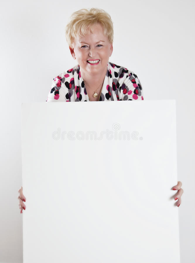 Mulher sênior que prende um sinal branco em branco