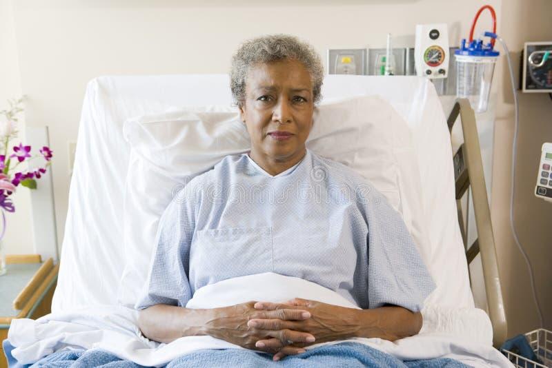 Mulher sênior que senta-se na cama de hospital fotografia de stock royalty free