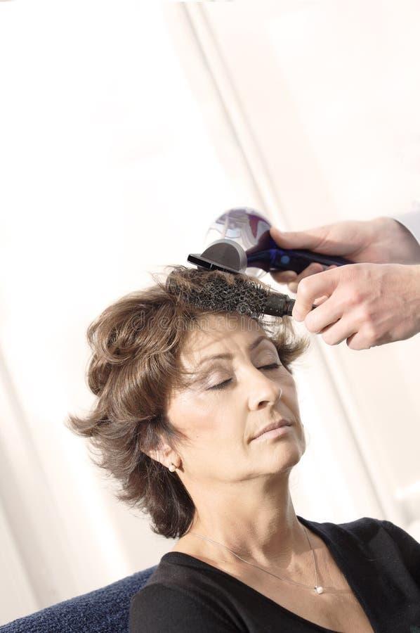 Mulher sênior que tem o corte de cabelo fotografia de stock