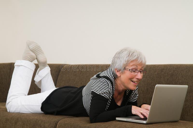 Mulher sênior que trabalha em um portátil fotografia de stock royalty free