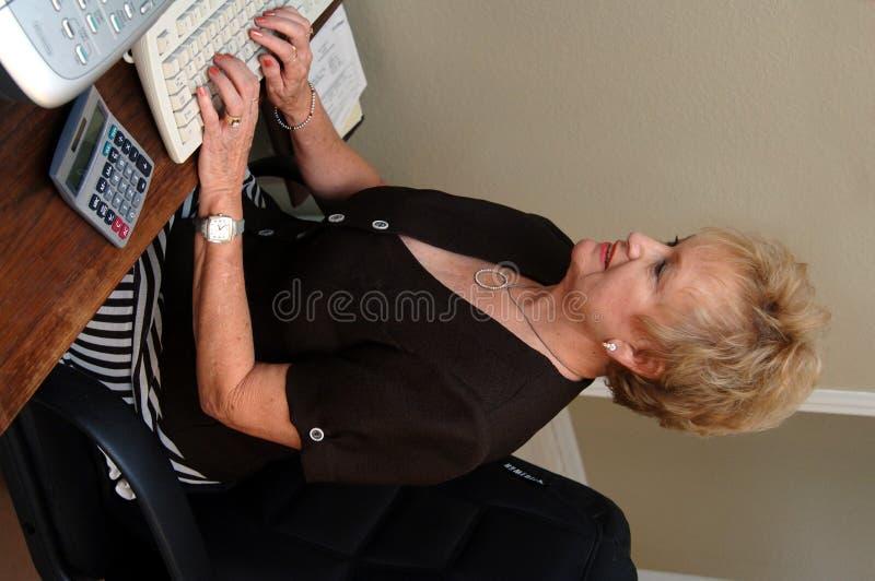 Mulher sênior que trabalha no escritório fotos de stock royalty free