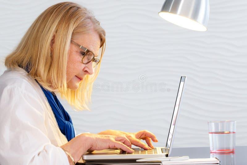 Mulher sênior que trabalha no portátil imagens de stock