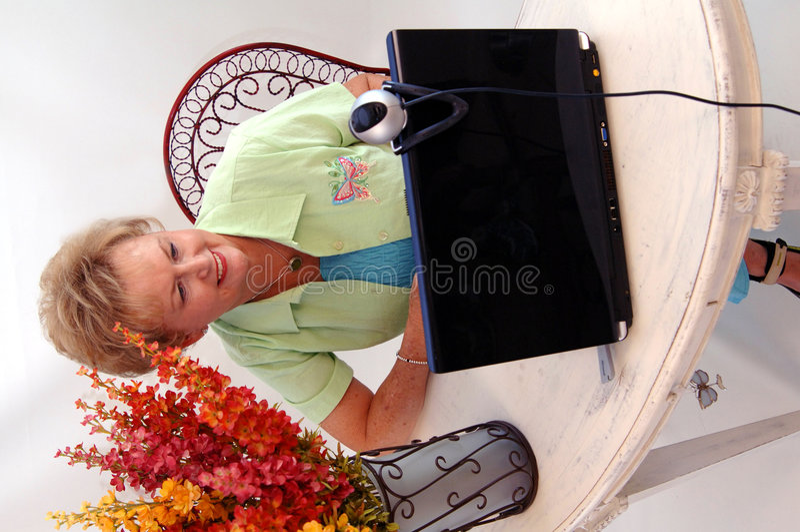 Mulher sênior que usa a câmara web imagem de stock