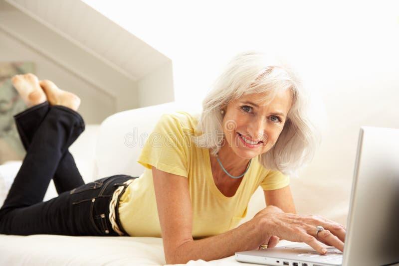 Mulher sênior que usa o assento de relaxamento do portátil no sofá imagem de stock