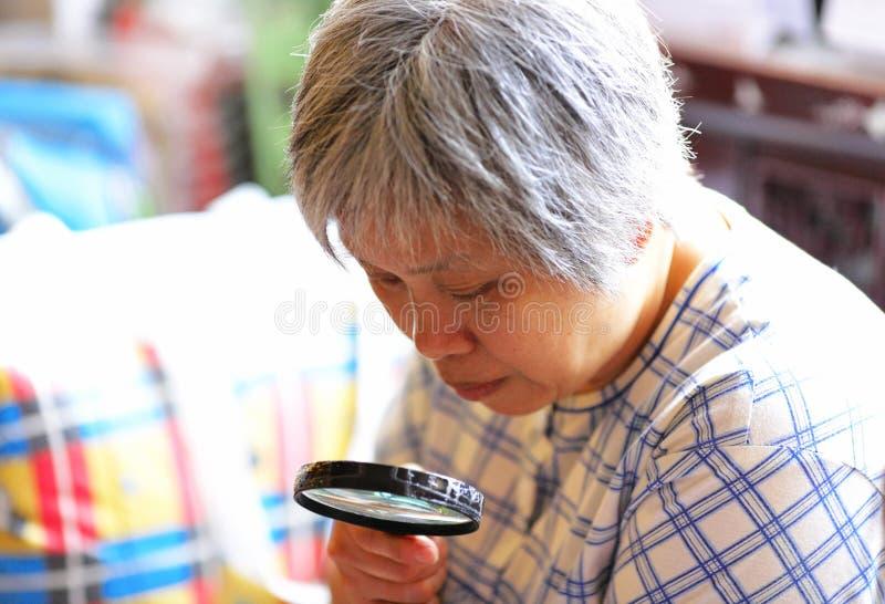 Mulher sênior que usa o magnifier fotografia de stock royalty free