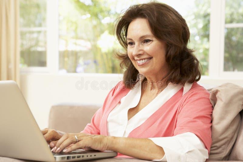 Mulher sênior que usa o portátil em casa imagens de stock