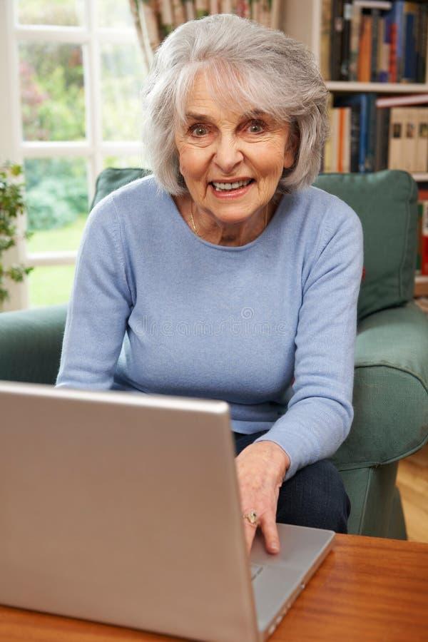 Mulher sênior que usa o portátil em casa imagens de stock royalty free